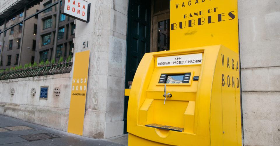 """位于伦敦市中心的一个叫""""Vagabond Wines""""的葡萄酒酒吧,异想天开地建造了一个神似ATM的黄色机器。路过的行人不用正儿八经地在店内消费,只要手持酒杯,在街边拧开机器上的龙头,就可以乘到流淌而出的普洛塞克(Prosecco),新鲜又便捷!"""